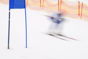 Ski racer runs by blue slalom gate